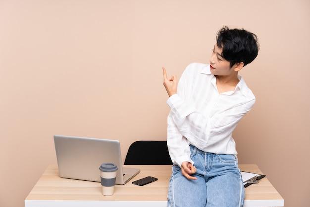 Jeune femme asiatique d'affaires dans son lieu de travail pointant vers l'arrière avec l'index