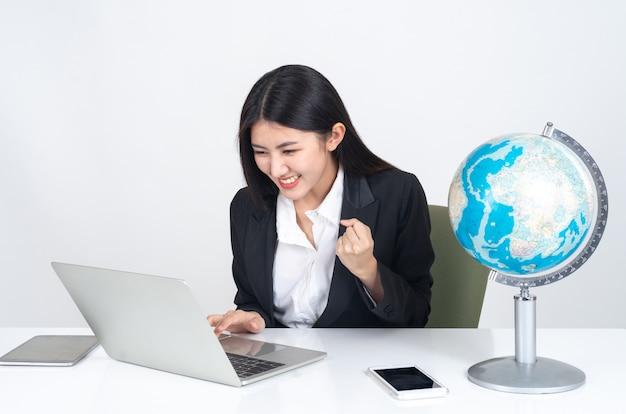 Jeune femme asiatique à l'aide d'un ordinateur portable et d'un téléphone intelligent sur le bureau