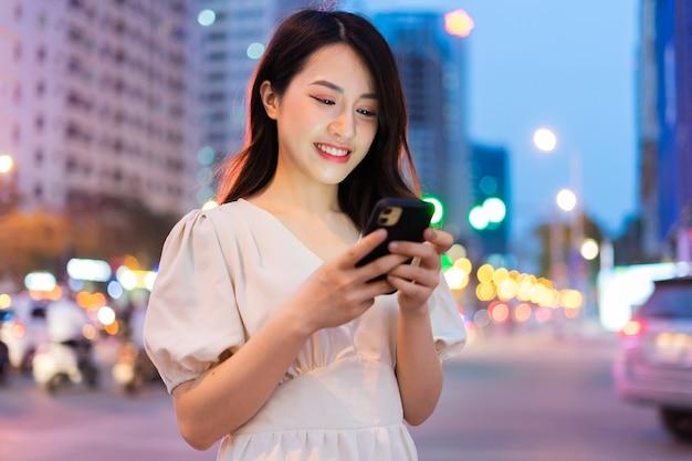 Jeune femme asiatique à l'aide de smartphone dans la rue pendant la nuit