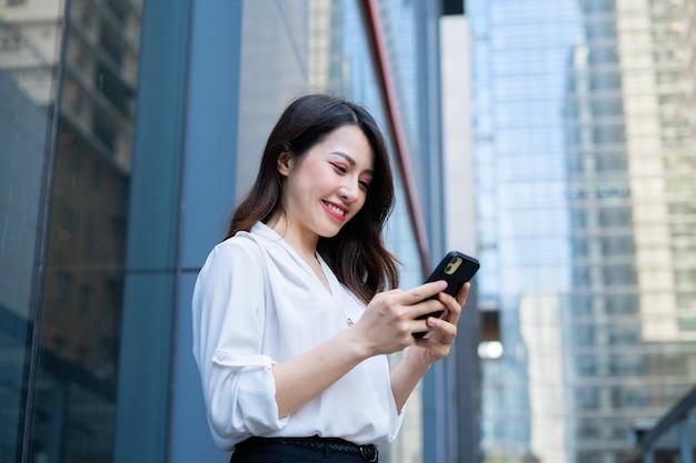 Jeune femme asiatique à l'aide de smartphone pour envoyer un sms à ses amis