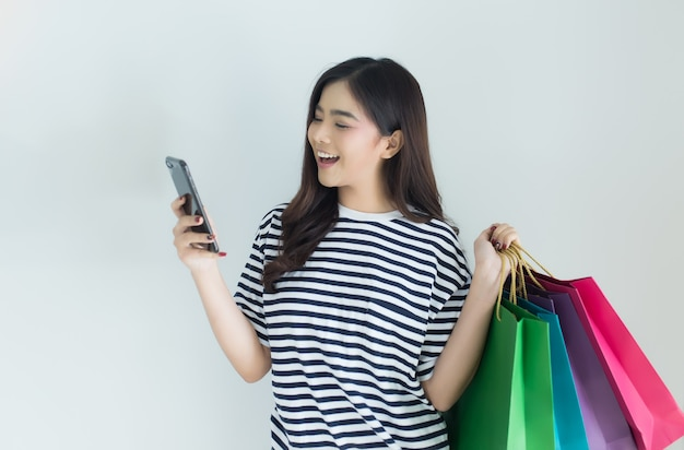 Jeune femme asiatique à l'aide de smartphone et tenant des sacs à provisions.