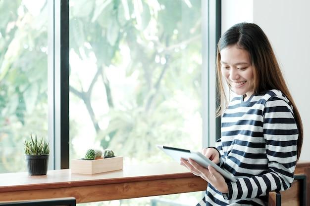 Jeune femme asiatique à l'aide de tablette en position assise par le fond de la fenêtre de café