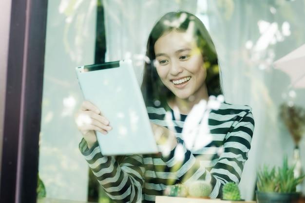 Jeune femme asiatique à l'aide de la tablette en position assise par le fond de la fenêtre de café