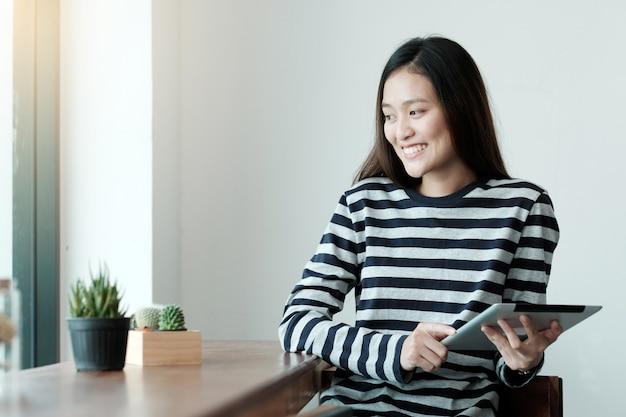 Jeune femme asiatique à l'aide de tablette tout en étant assis au café fond