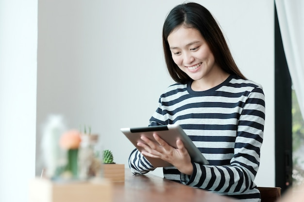 Jeune femme asiatique à l'aide de la tablette tout en étant assis par le fond de la fenêtre de la fenêtre, la technologie des personnes et le style de vie
