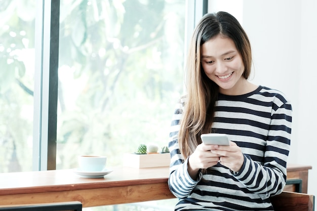 Jeune femme asiatique à l'aide de téléphone intelligent tout en étant assis par le fond de la fenêtre de café