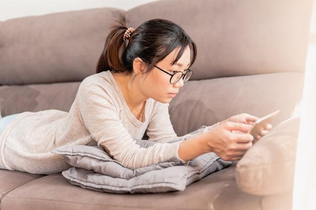 Jeune femme asiatique allongée sur le canapé à la maison, regarder des vidéos et des films sur un ipad.