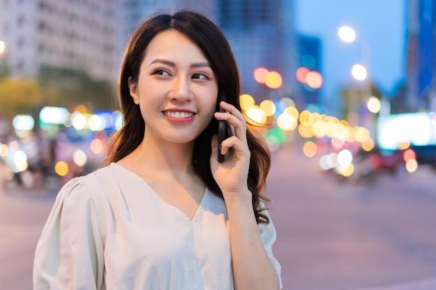 Jeune femme asiatique appelant en marchant dans la rue pendant la nuit