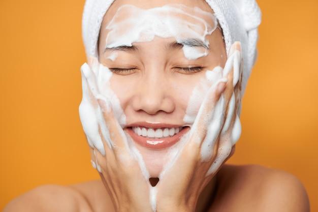 Jeune femme asiatique appliquant de la crème sur son visage et touchant le visage tout en portant une serviette de bain. isolé sur fond orange.