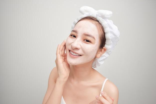 Jeune femme asiatique appliquant un masque d'argile pour le visage sur fond blanc. concept de soins de beauté.