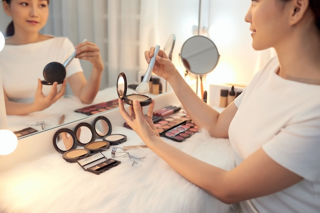 Jeune femme asiatique appliquant de la poudre avec un gros pinceau. notion de cosmétiques