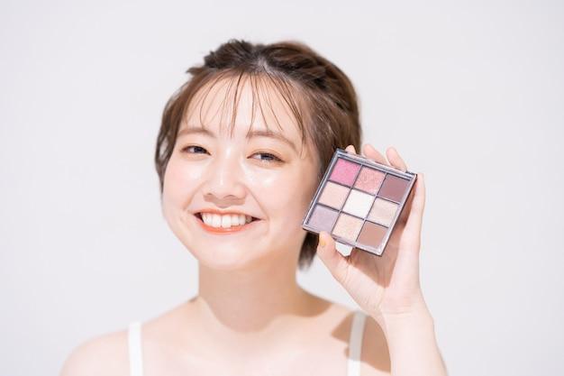 Jeune femme asiatique avec des articles cosmétiques et fond blanc