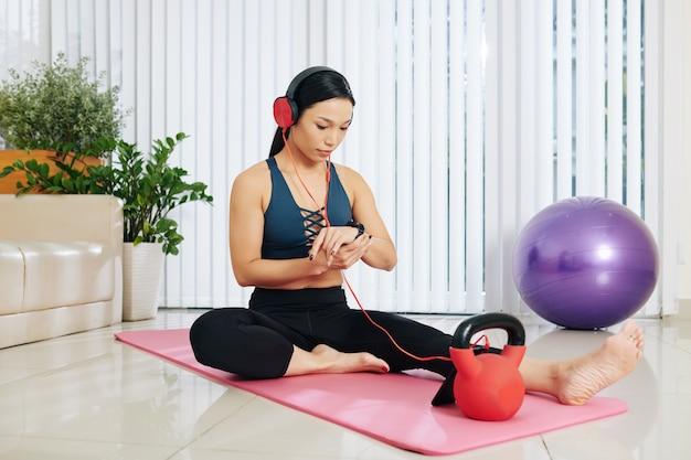Jeune femme asiatique assez en forme se reposant sur un tapis de yoga après s'être entraînée à la maison et avoir vérifié l'application de santé sur sa montre intelligente