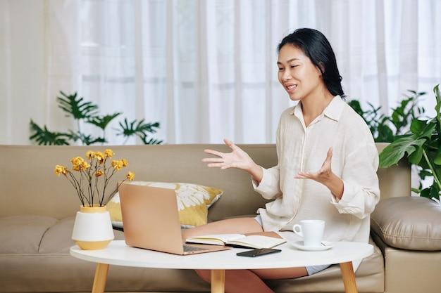 Jeune femme asiatique assez positive ayant une réunion en ligne avec des collègues ou des camarades étudiants