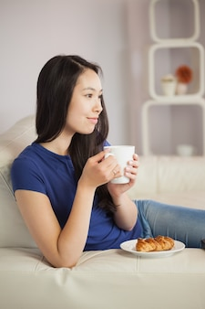 Jeune femme asiatique assise sur le canapé en train de prendre un café