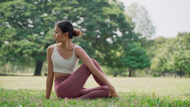 Jeune femme asiatique assise sur l'herbe dans la position du lotus