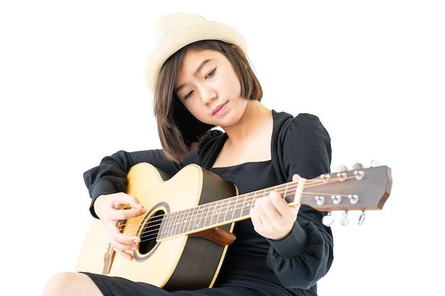 Jeune femme asiatique assise et jouant de la guitare chanson folklorique de guitare dans sa main isoler sur fond blanc