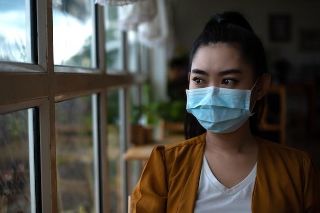 Jeune femme asiatique assise et mettant un masque médical