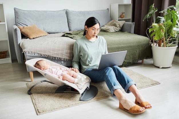 Jeune femme asiatique assise par terre dans la pièce travaillant en ligne sur un ordinateur portable et s'occupant d'elle allumée...