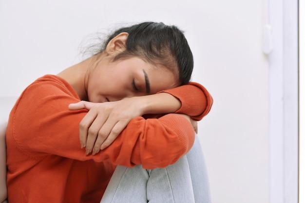 Jeune femme asiatique assise sur le sol et se sentant fatiguée