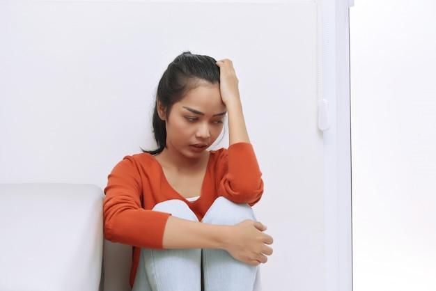 Jeune femme asiatique assise sur le sol et se sentir seule