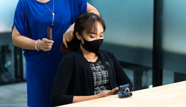 Jeune femme asiatique au salon de coiffure portant un masque protecteur chirurgical. nouveau concept de distanciation normale et sociale