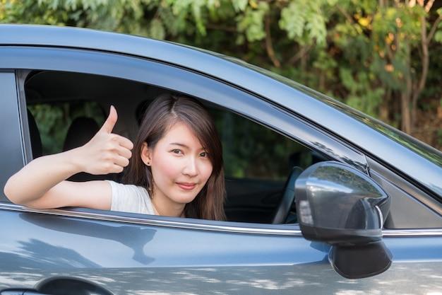 Jeune femme asiatique au volant d'une voiture