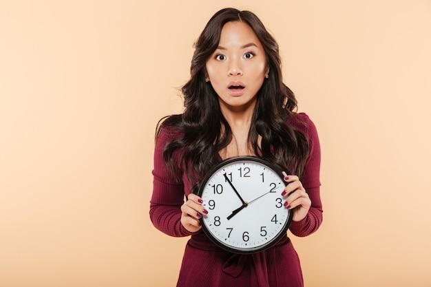 Jeune femme asiatique aux cheveux longs bouclés tenant une horloge montrant près de 8 étant en retard ou manquant quelque chose sur fond de pêche