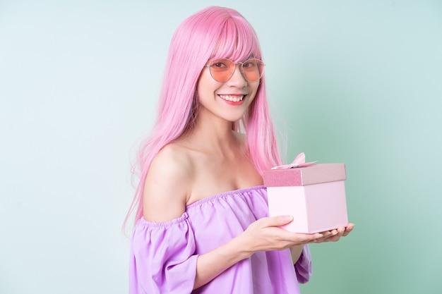 Jeune femme asiatique aux cheveux roses posant sur fond vert