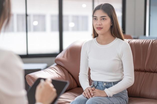 Une jeune femme asiatique ayant un problème de santé mentale rencontre un psychologue à consulter et une thérapie mentale. concept de psychologie et de thérapie mentale