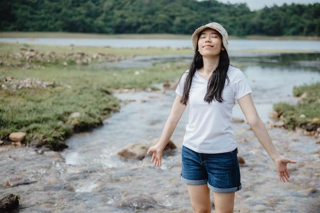 Jeune femme asiatique ayant profiter et se détendre avec la nature, champ de ruisseau d'eau, cascade en plein air