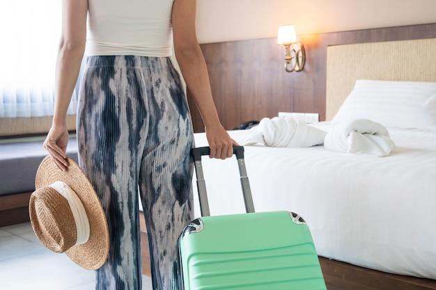 Jeune femme asiatique avec des bagages verts et chapeau de paille dans la chambre d'hôtel après l'enregistrement