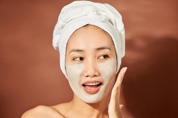 Jeune femme asiatique bénéficiant d'un traitement de masque facial.