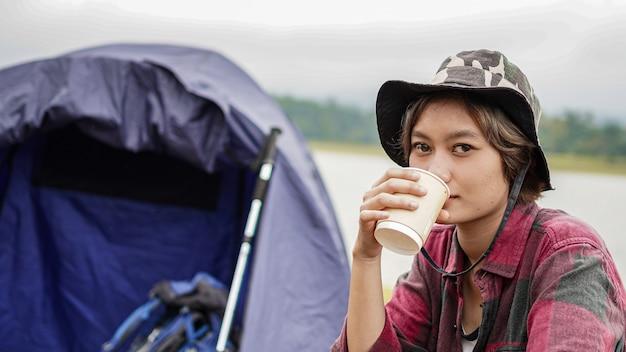 Jeune femme asiatique boire du café sur une chaise