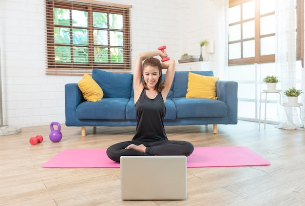 Jeune femme asiatique en bonne santé dans l'entraînement de vêtements de sport à la maison, exercice, ajustement, faire du yoga. concept de remise en forme sport à domicile