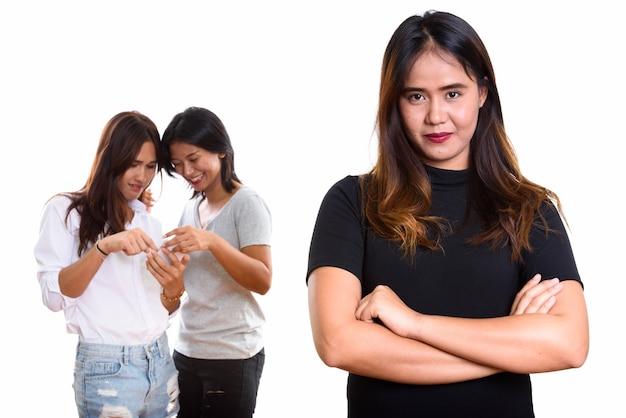 Jeune femme asiatique avec les bras croisés avec deux amis heureux à l'arrière à l'aide de téléphone mobile ensemble