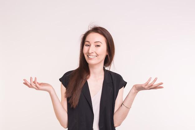 Jeune femme asiatique brune hausse les épaules sur blanc.