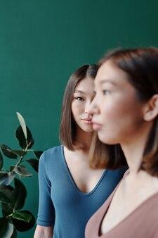 Jeune femme asiatique brune en tenue décontractée vous regarde en se tenant derrière sa sœur jumelle contre une plante domestique et un mur vert foncé