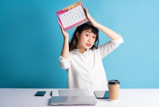 Jeune femme asiatique buisness travaillant sur bleu