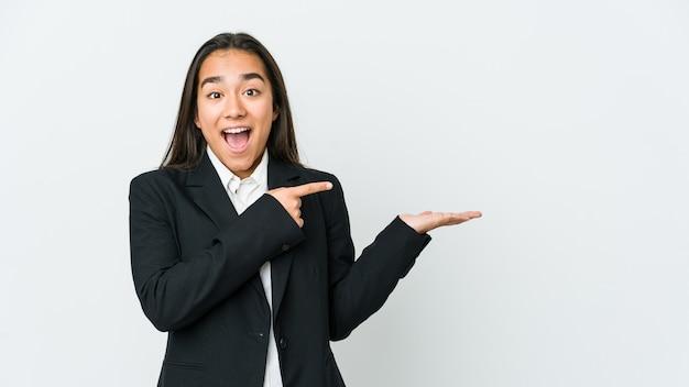 Jeune femme asiatique bussines isolé sur mur blanc excité tenant un espace de copie sur la paume