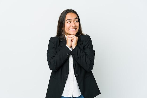 Jeune femme asiatique bussines isolée sur un mur blanc garde les mains sous le menton, regarde joyeusement de côté