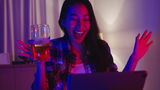 Jeune femme asiatique buvant de la bière s'amusant moment heureux disco néon soirée fête événement en ligne célébration par appel vidéo dans le salon à la maison.