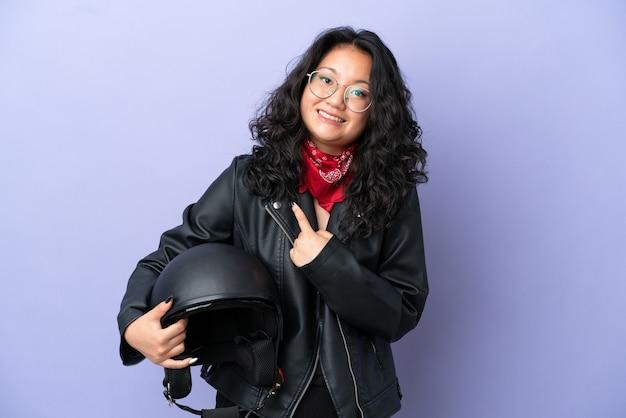 Jeune femme asiatique avec un casque de moto isolé sur fond violet avec une expression faciale surprise
