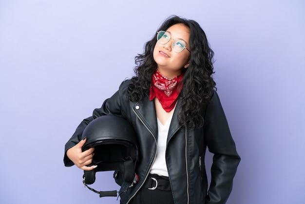 Jeune femme asiatique avec un casque de moto isolé sur fond violet en pensant à une idée tout en levant les yeux