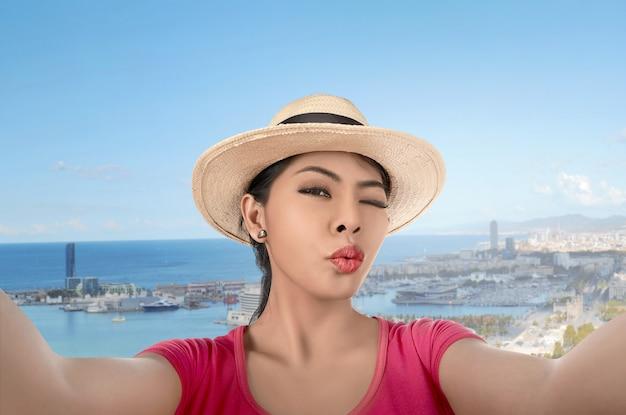 Jeune femme asiatique avec chapeau prenant selfie posant
