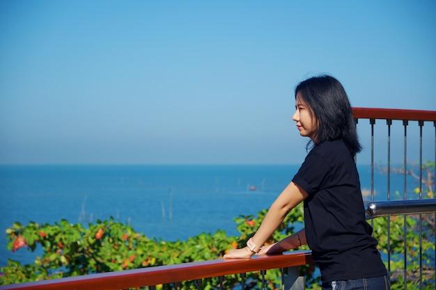 Jeune femme asiatique en chemise noire debout et impatient au point de vue de la mer