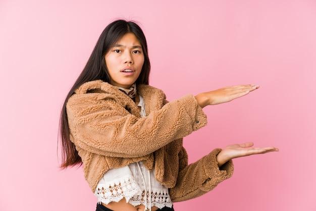 Jeune femme asiatique choquée et étonnée tenant un espace vide entre les mains.