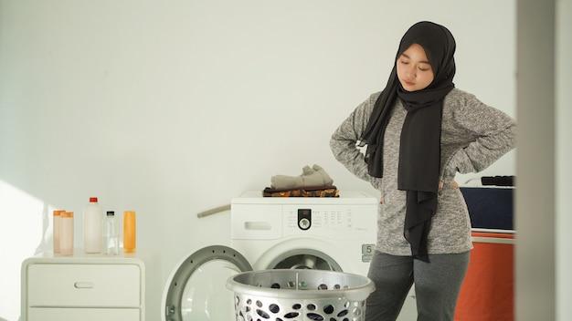 Jeune femme asiatique contrariée de voir un panier de vêtements sales à la maison