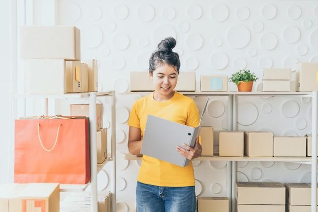 Jeune femme asiatique contrôle des marchandises sur l'étagère de stock à l'entrepôt