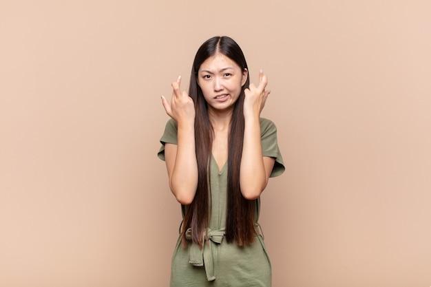 Jeune femme asiatique croisant les doigts avec anxiété et espérant bonne chance